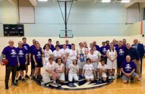 """Special Olympic Athletes and Community Members pose for a photo after finishing up the """"Celebrity Basketball Game"""", which is a part of DD Awareness Month in March."""