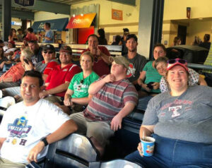 Members of the Recreation Program smile for a photo while sitting in the stands at a Mudhens game.