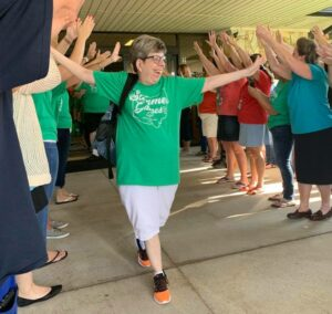 A Special Olympics Athlete high fives staff members before heading out to State Games.