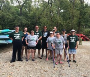 Image Description: Venturing Crew members stand on a beach and pose for a photo before going on a canoe trip.